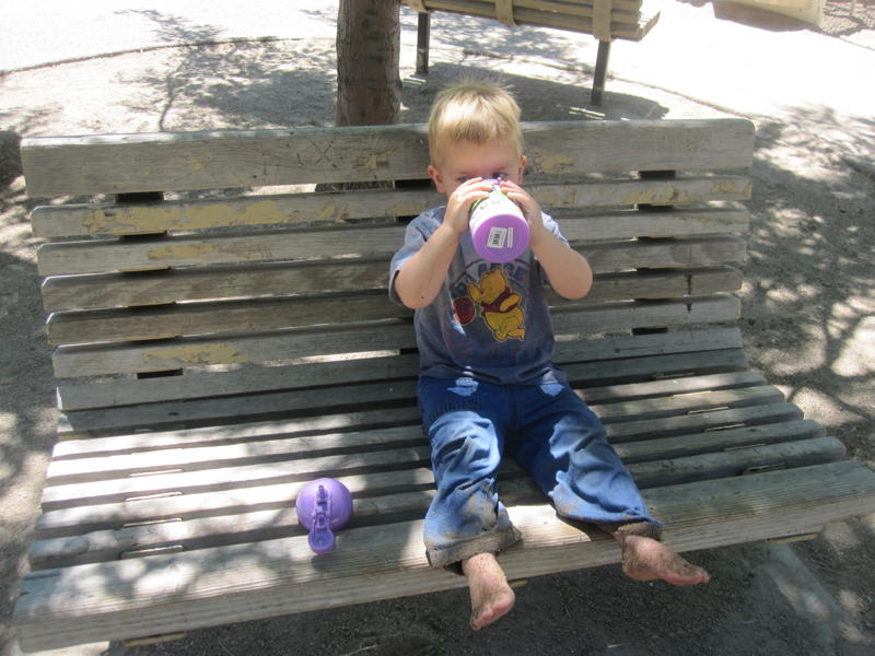 kid drinking water on bench picture
