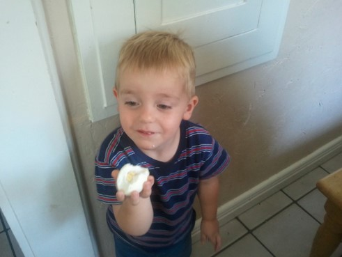 little boy eating an oval hard boiled egg
