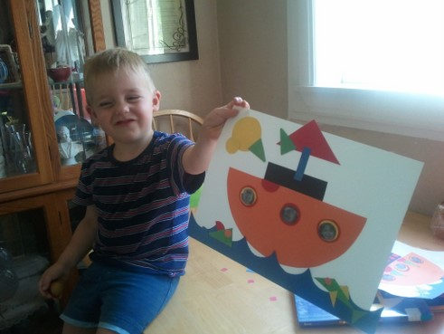 little boy with the shaped ship picture he made