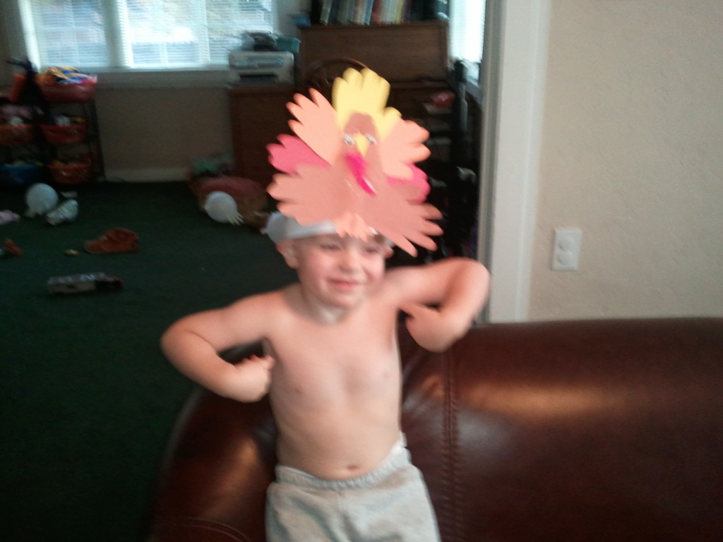 little boy with turkey crown and doing a turkey dance