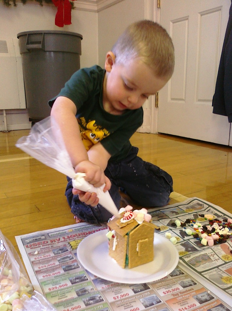 little boy making gingerbread house